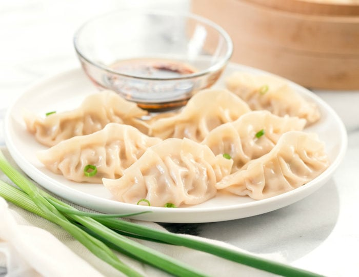 photo of jiaozi on a plate with dipping sauce