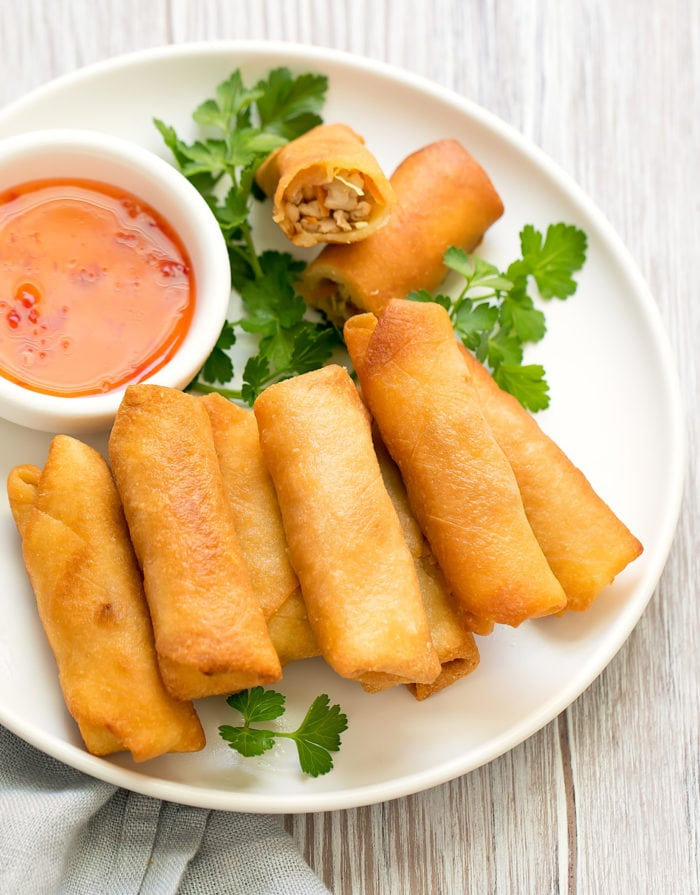 overhead photo of eggrolls on a plate with sauce