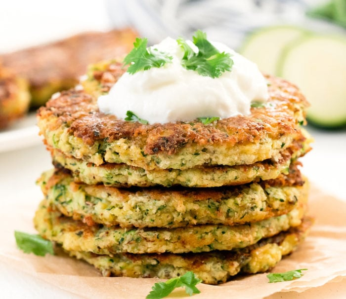 close-up photo of zucchini fritters topped with sour cream