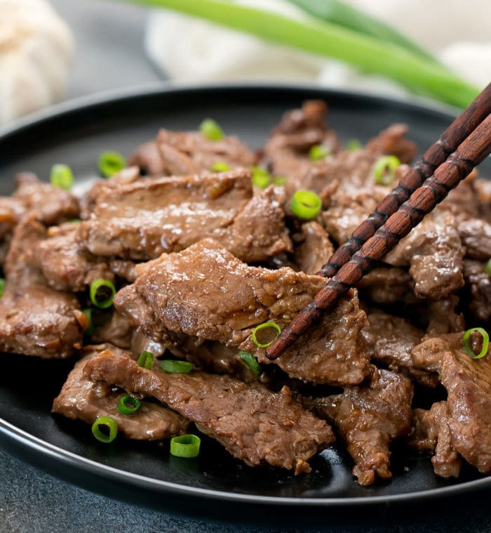 photo of chopsticks holding a piece of garlic beef