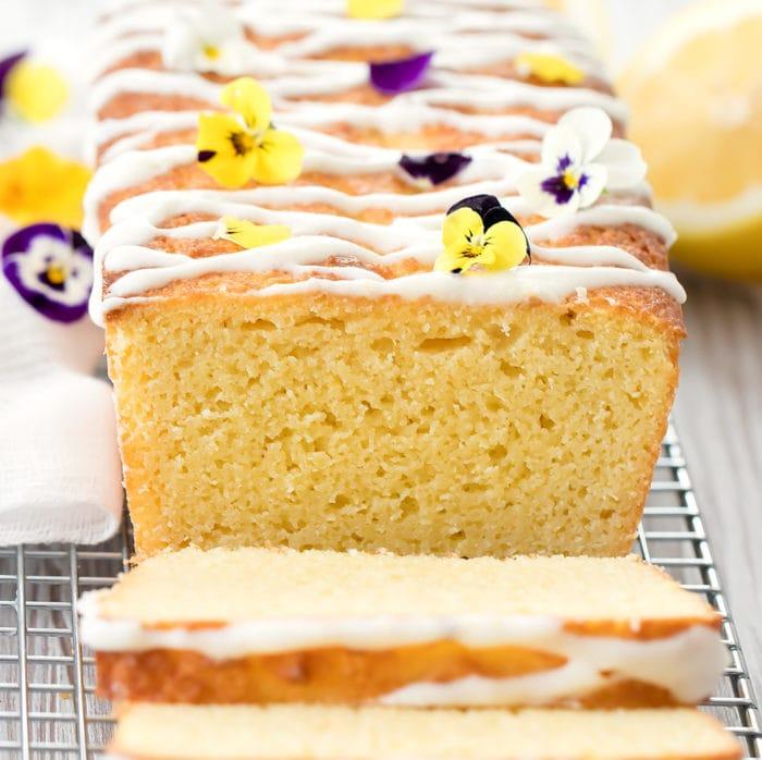 photo of a lemon cake garnished with glaze and fresh flowers