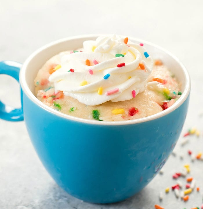 photo of a mug cake topped with whipped cream and sprinkles