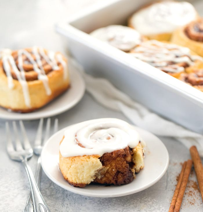 photo of cinnamon rolls on plates with a pan in the background