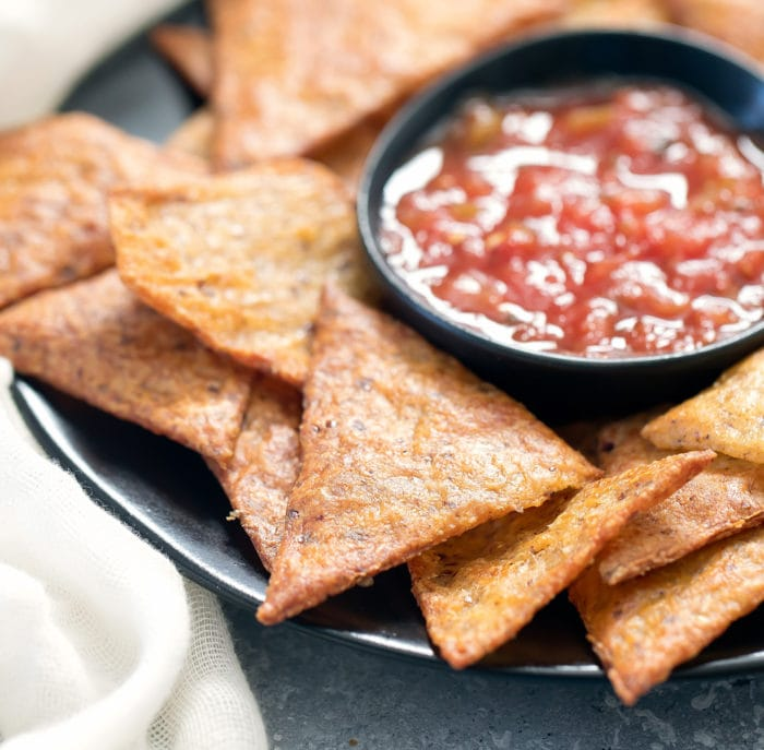 close-up photo of the chips on a plate with a bowl of salsa