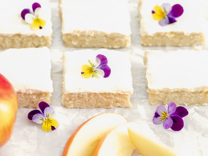 slices of apple cake decorated with fresh flowers.