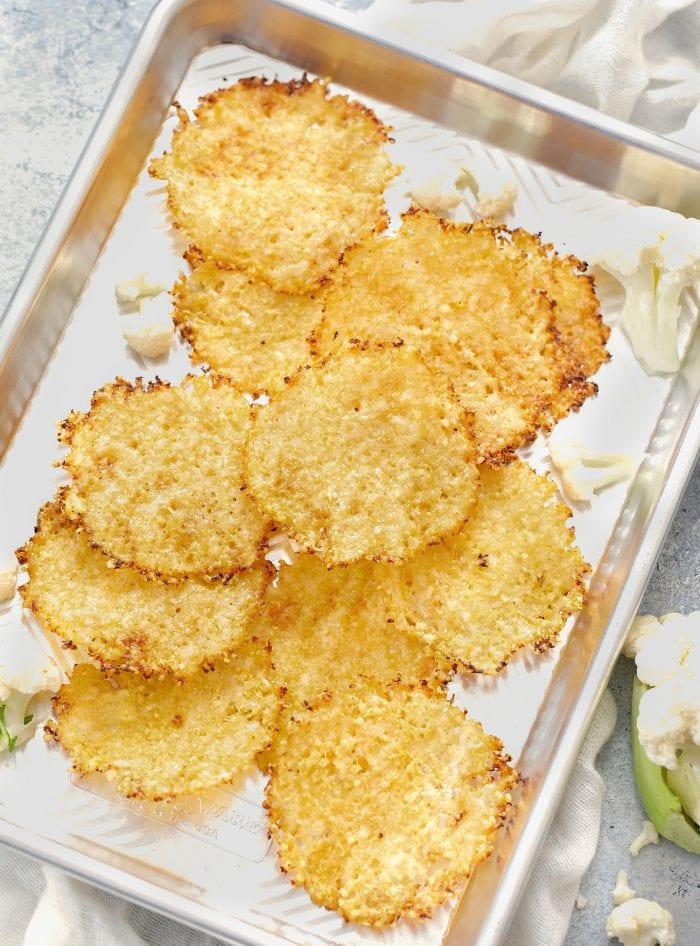 overhead shot of cauliflower chips on a sheet pan.