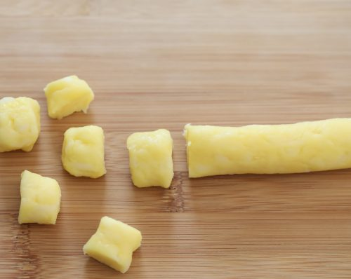a roll of cheese dough with pieces sliced off.
