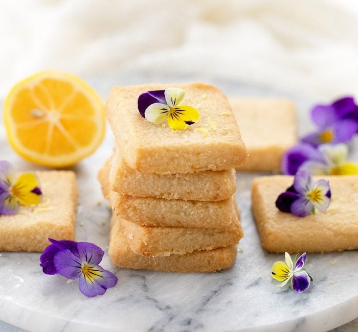a stack of cookies garnished with fresh flowers.