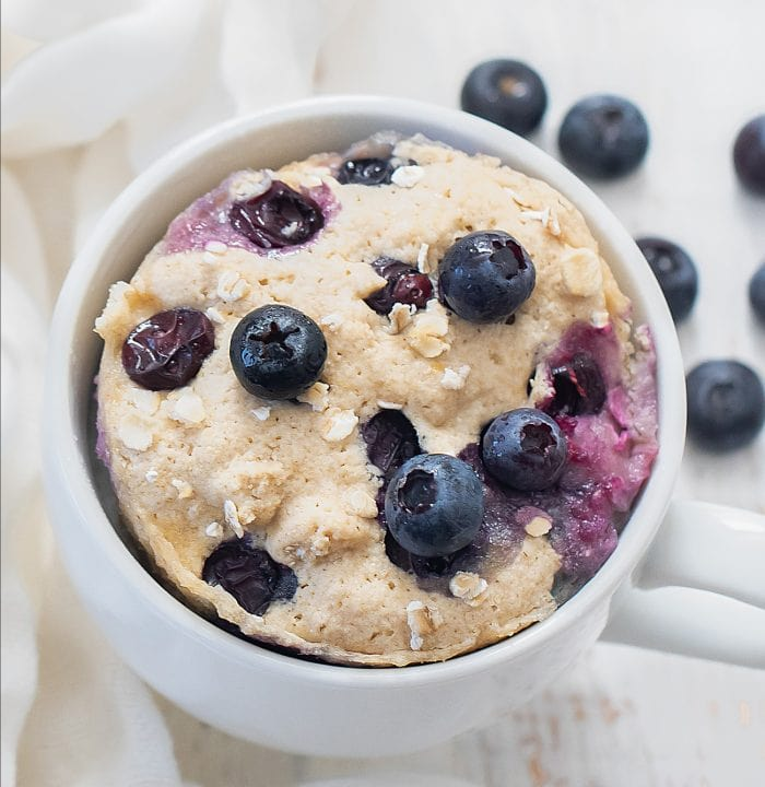 overhead shot of a blueberry muffin in a mug.