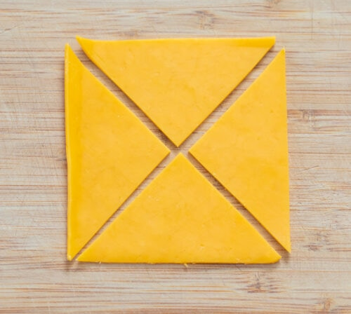 a slice of cheese cut into four triangles.