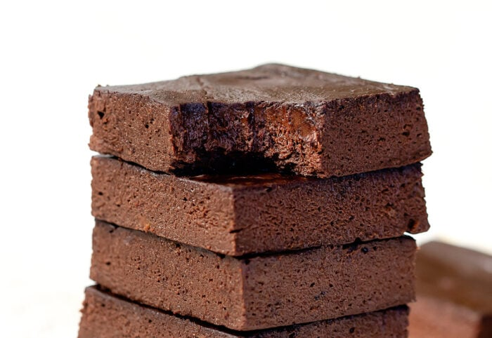 a brownie on top of a stack with a bite taken out of it.