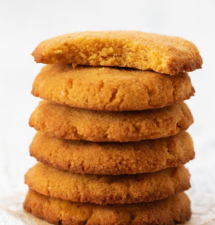 five cookies stacked with a bite taken out of the top one.